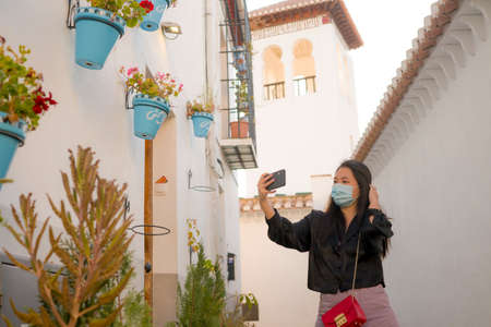 new normal travel and tourism - young happy and beautiful Asian Japanese woman in anti virus mask taking selfie with mobile phone enjoying Summer holidays in Spain after lockdown 版權商用圖片