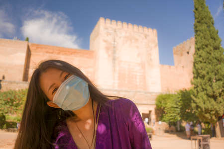 new normal travel and tourism - young happy and beautiful Asian Korean woman in anti virus mask carefree and cheerful enjoying Summer holidays in Spain after lockdown 版權商用圖片
