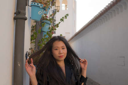 lifestyle portrait of young beautiful and happy Asian Chinese woman enjoying Summer holidays in Europe walking cheerful at Spain Andalusia village in tourism and travel concept
