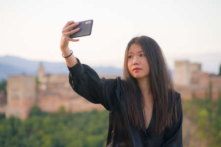 lifestyle portrait of young beautiful and happy Asian Japanese tourist woman having Summer holidays in Europe taking selfie with mobile phone at beautiful Alhambra of Granada in Spain