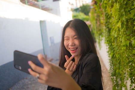 young happy and beautiful Asian Chinese woman enjoying outdoors taking selfie with mobile phone at village garden playful and carefree in beauty fashion and freedom concept