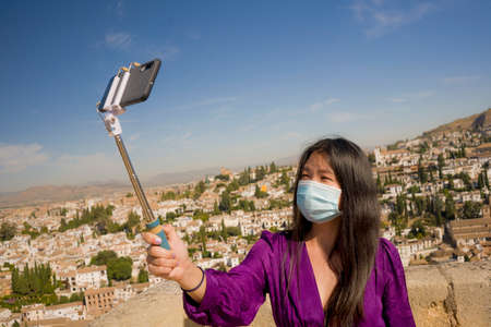 new normal travel and tourism - young happy and beautiful Asian Chinese woman in anti virus mask taking selfie with mobile phone enjoying Summer holidays in Spain after lockdown