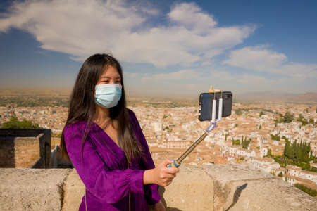 new normal travel and tourism - young happy and beautiful Asian Korean woman in anti virus mask taking selfie with mobile phone enjoying Summer holidays in Spain after lockdown