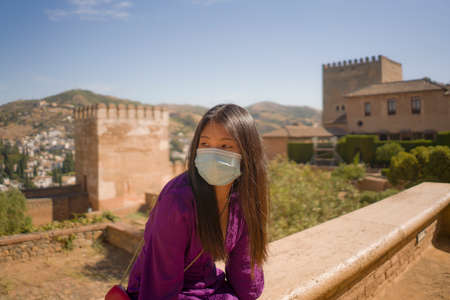 new normal travel and tourism - young happy and beautiful Asian Chinese woman in anti virus mask carefree and cheerful enjoying Summer holidays in Spain after lockdown