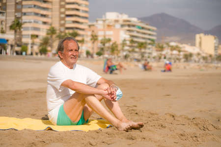 Senior pensioner sitting relaxed on the beach - retired old man on his 70s looking at the sea thoughtful and contemplative with surgical mask on his hands in health concept