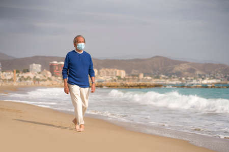 Senior pensioner relaxed in beach during new normal - retired old man on his 70s wearing surgical mask against covid19 walking at the sea thoughtful and contemplative in health concept