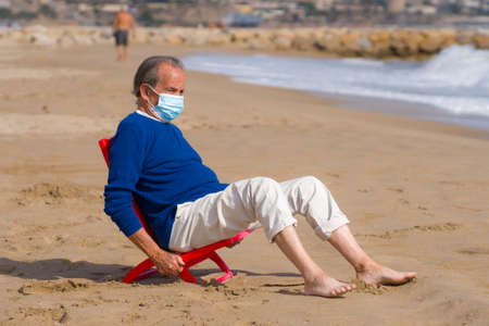 Senior pensioner taking a walk relaxed on the beach - retired old man on his 70s looking at the sea thoughtful and contemplative with surgical mask on his hand in health concept 版權商用圖片