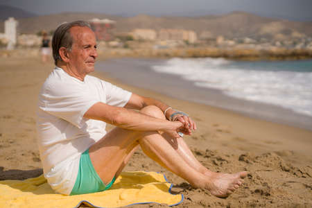 Senior pensioner sitting relaxed on the beach - retired old man on his 70s looking at the sea thoughtful and contemplative in health concept