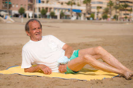Senior pensioner sitting relaxed on the beach - retired old man on his 70s looking at the sea thoughtful and contemplative with surgical mask on his arm in health concept