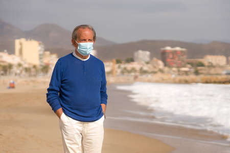 Senior pensioner taking a walk relaxed on the beach - retired old man on his 70s looking at the sea thoughtful and contemplative with surgical mask on his hand in health concept Stockfoto
