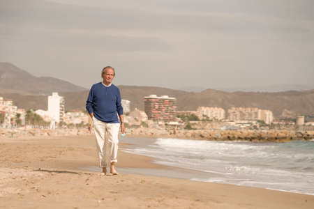 Senior pensioner taking a walk relaxed on the beach - retired old man on his 70s looking at the sea thoughtful and contemplative with surgical mask on his hand in health concept