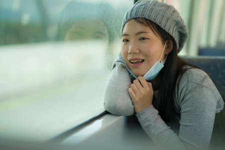 lifestyle portrait of young attractive and pretty Asian woman wearing mask in railcar traveling in new normal virus time - sweet Japanese girl by train window smiling cheerful