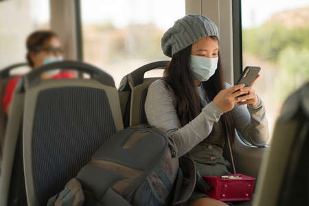 new normal traveling - young attractive and pretty Asian Korean woman in face mask sitting on railcar by window using internet mobile phone in the train relaxed