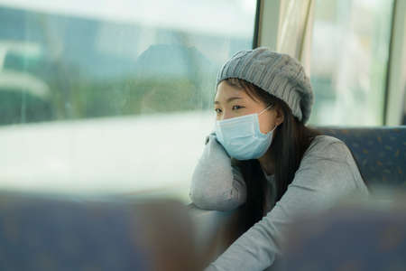 lifestyle portrait of young attractive and pretty Asian woman wearing mask in railcar traveling in new normal virus time - sweet Chinese girl by train window smiling cheerful