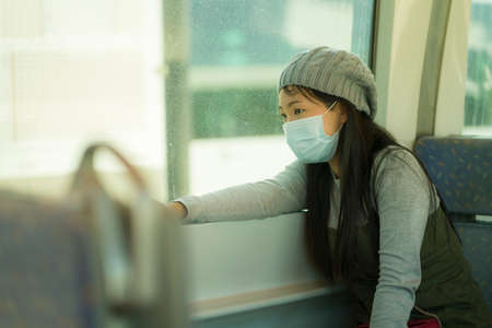 lifestyle portrait of young attractive and pretty Asian woman wearing mask in railcar traveling in new normal virus time - sweet Chinese girl by train window thoughtful and pensive