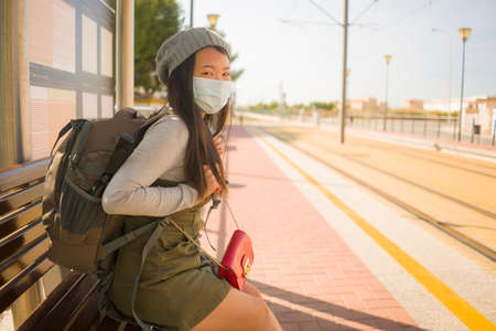 young beautiful and happy tourist Asian woman traveling during new normal - attractive Chinese girl with backpack waiting for train at station platform doing tourism while virus