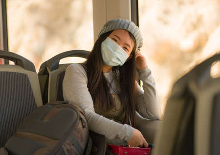 lifestyle portrait of young attractive and pretty Asian woman wearing mask in railcar traveling in new normal virus time - sweet Japanese girl by train window happy and excited