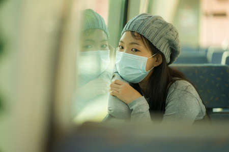 lifestyle portrait of young attractive and pretty Asian woman wearing mask in railcar traveling in new normal virus time - sweet Korean girl by train window smiling cheerful