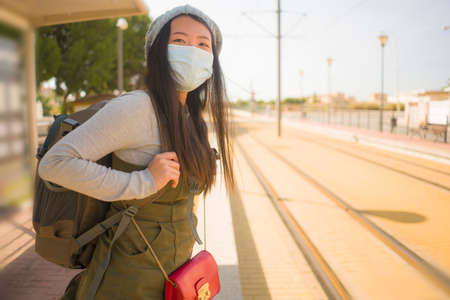 young happy and attractive Asian woman traveling during new normal - beautiful Korean girl with backpack waiting for train at station platform as tourism in virus time