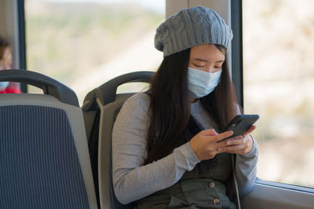 new normal traveling - young attractive and pretty Asian Chinese woman in face mask sitting on railcar by window using internet mobile phone in the train relaxed