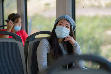 new normal traveling - young attractive and pretty Asian Chinese woman in face mask sitting on railcar by window enjoying trip in the train relaxed and thoughtful