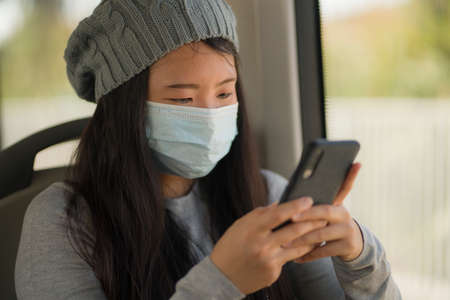 new normal traveling - young attractive and pretty Asian Japanese woman in face mask sitting on railcar by window using internet mobile phone in the train relaxed 版權商用圖片