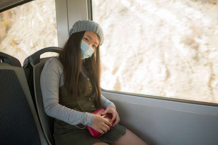 new normal traveling - young attractive and pretty Asian Korean woman in face mask sitting on railcar by window enjoying trip in the train relaxed and thoughtful