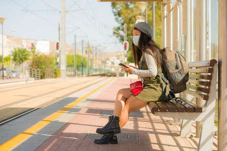 young happy and beautiful Asian woman traveling during new normal - attractive Korean girl with backpack waiting for train at station platform as tourism in virus time