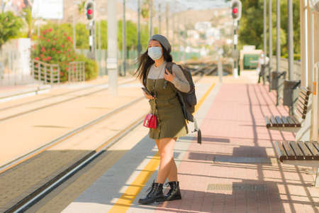 young happy and attractive Asian woman traveling during new normal - beautiful Chinese girl with backpack waiting for train at station platform as tourism in virus time