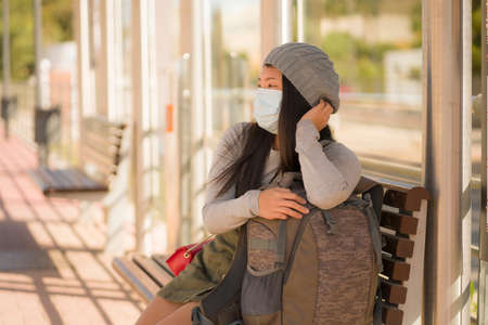 young beautiful and happy tourist Asian woman traveling during new normal - attractive Japanese girl with backpack waiting for train at station platform doing tourism while virus