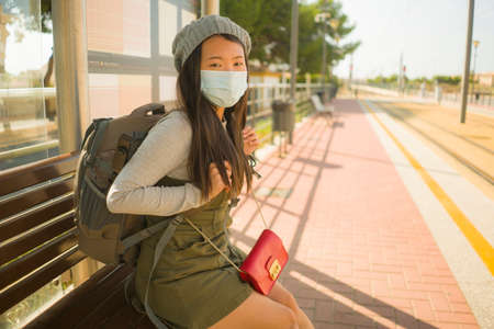 young beautiful and happy tourist Asian woman traveling during new normal - attractive Korean girl with backpack waiting for train at station platform doing tourism while virus