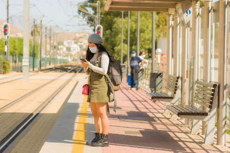 young happy and beautiful Asian woman traveling during new normal - attractive Japanese girl with backpack waiting for train at station platform as tourism in virus time