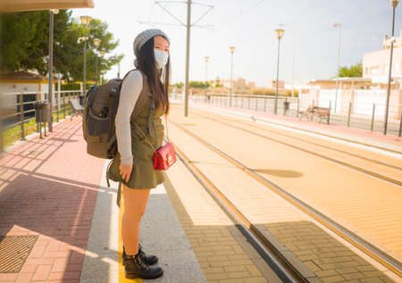 young happy and attractive Asian woman traveling during new normal - beautiful Japanese girl with backpack waiting for train at station platform as tourism in virus time