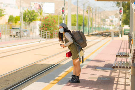 young happy and beautiful Asian woman traveling during new normal - attractive Chinese girl with backpack waiting for train at station platform as tourism in virus time