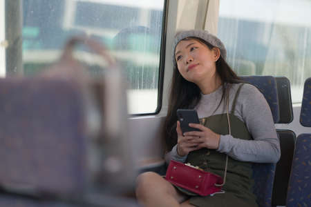 lifestyle portrait of young beautiful and attractive Asian Korean woman in winter hat looking thoughtful through window on train using internet mobile phone