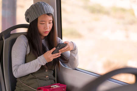 lifestyle portrait of young beautiful and attractive Asian Japanese woman in winter hat sitting by window on train using internet mobile phone in transportation concept