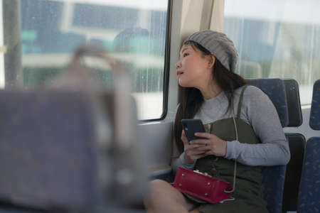 lifestyle portrait of young beautiful and attractive Asian Japanese woman in winter hat looking thoughtful through window on train using internet mobile phone