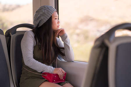 young beautiful and attractive Asian Chinese woman in winter hat sitting relaxed on train looking through window enjoying traveling in tourism and lifestyle concept