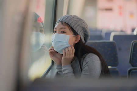 young attractive and happy Asian woman in mask traveling on railcar in new normal virus time - sweet Korean girl looking through train window excited and cheerful
