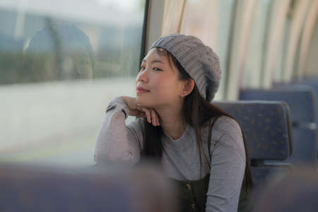 lifestyle portrait of young happy and beautiful Asian Korean woman excited and cheerful looking through window sitting on train enjoying landscape from the railcar glass