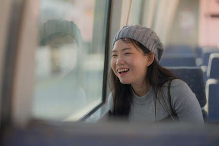 lifestyle portrait of young happy and beautiful Asian Japanese woman excited and cheerful looking through window sitting on train enjoying landscape from the railcar glass