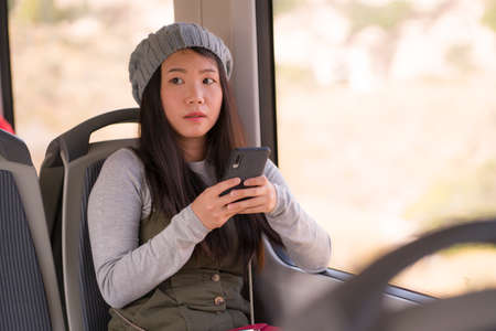 lifestyle portrait of young beautiful and attractive Asian Korean woman in winter hat sitting by window on train using internet mobile phone in transportation concept 版權商用圖片