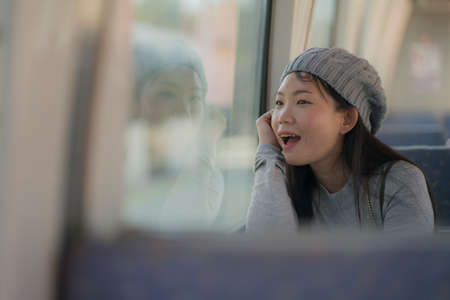 lifestyle portrait of young happy and beautiful Asian Chinese woman excited and cheerful looking through window sitting on train enjoying landscape from the railcar glass 版權商用圖片