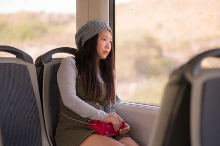 young beautiful and attractive Asian Korean woman in winter hat sitting relaxed on train looking through window enjoying traveling in tourism and lifestyle concept