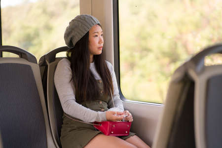 young beautiful and attractive Asian Japanese woman in winter hat sitting relaxed on train looking through window enjoying traveling in tourism and lifestyle concept 版權商用圖片