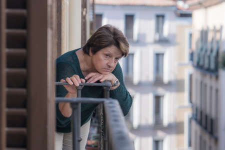 dramatic lifestyle portrait of mature woman on her 70s depressed and sad at home balcony feeling desperate suffering anxiety problem in senior female depression concept