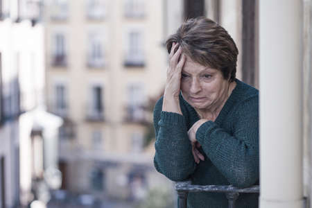 dramatic lifestyle portrait of mature woman on her 70s crying depressed and sad at home balcony feeling desperate suffering anxiety problem in senior female depression concept