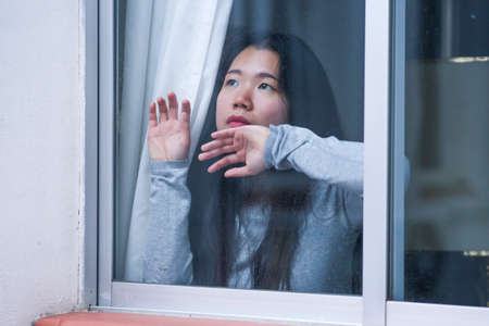 girl in stress at home - dramatic portrait of young sad and depressed Asian Japanese woman on window feeling worried and desperate during covid19 stay home and lockdown