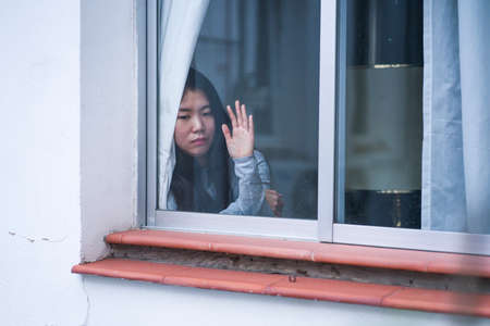 girl in stress at home - dramatic portrait of young sad and depressed Asian Korean woman on window feeling worried and desperate during covid19 stay home and lockdown