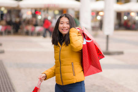 Asian girl enjoying Christmas shopping - young happy and beautiful Japanese woman holding red shopping bag buying presents at street xmas market smiling cheerful